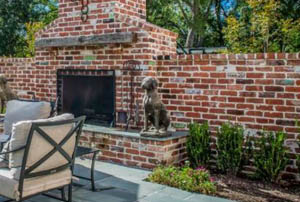 This picture shows brick wall contractors in San Diego. Fireplace is included in the brick wall, and floor is concrete patio