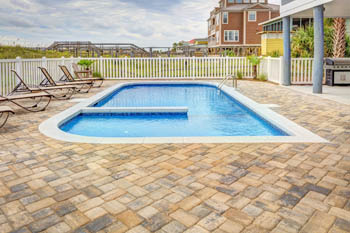 This picture shows a concrete and stone pavers in San Diego done by the swimming pool deck.