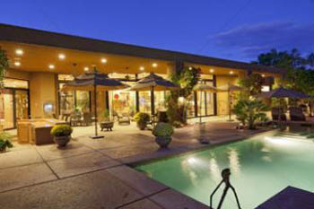 This picture shows a concrete patio builder in San Diego. It is made of concrete around the swimming pool.